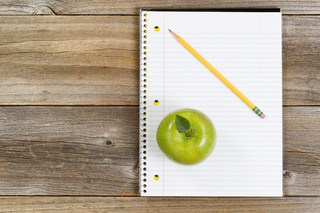 pencil and paper: Top view of green apple, notepad and pencil on rustic wood. Stock Photo