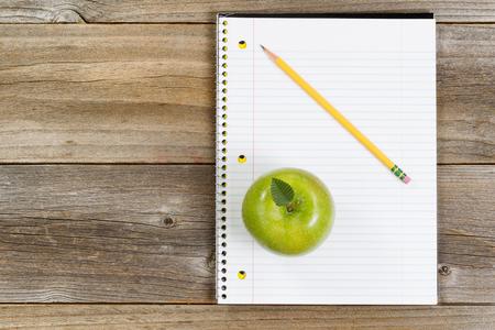 lapiz y papel: Vista superior de la manzana verde, bloc de notas y lápiz sobre madera rústica.