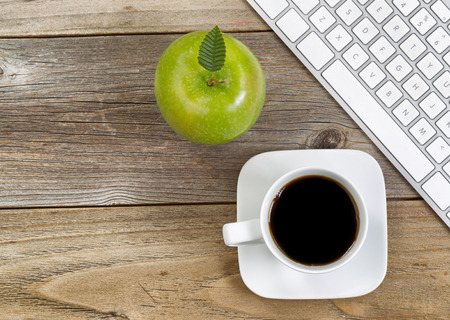 teclado de computadora: Top view of green apple, selective focus on top leaf and coffee, black coffee with partial computer keyboard on rustic wood. Foto de archivo