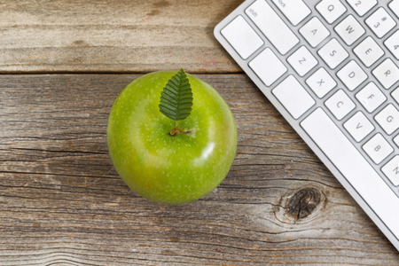 selective focus: Top view of green apple, selective focus on top leaf, with partial computer keyboard on rustic wood.