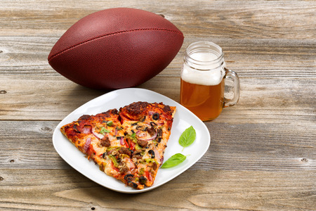 american cuisine: Two slices of freshly baked pizza in a white plate, football, and a pint of justly poured beer setting on rustic wooden table. Stock Photo
