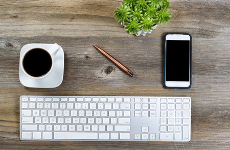 desk tidy: Top view of a neat desktop with keyboard, black coffee, green plant and cell phone on wooden desk. Stock Photo