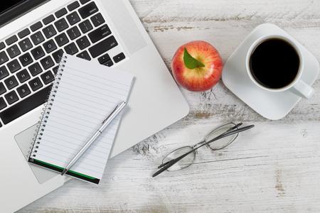 botanas: Vista superior de escritorio con ordenador portátil parcial, manzana, café, gafas de lectura, y la pluma. Foto de archivo