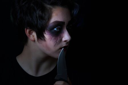 girl with knife: Teen girl masked in scary makeup with combat knife on black background.