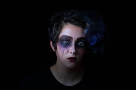 scary girl: Teen girl in scary makeup on black background.
