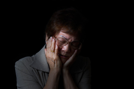 sad lady: Senior woman holding her face with both hands while displaying pain on black background.