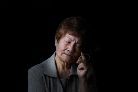 wrinkled: Senior woman displaying pain while holding reading glass on black background.