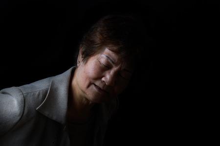 wrinkled: Senior woman bending forward while displaying pain on black background.