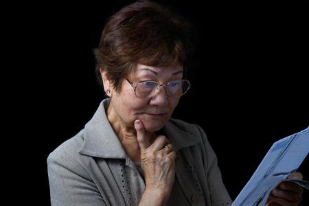 wrinkled: Senior woman looking surprised by her bills. Black background.