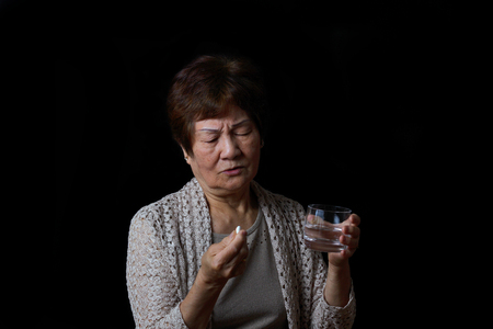 wrinkled: Senior woman preparing to take her medicine with water. Black background. Stock Photo