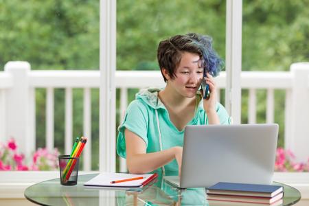 woman  laptop: Teen girl talking on cell while doing her homework. Large windows in background with blurred out bright green trees and flowers. Stock Photo