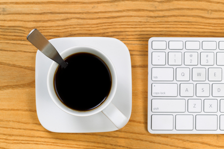 telecommute: Top view of desktop with coffee, selective focus on top of cup, and partial keyboard. Horizontal format. Stock Photo