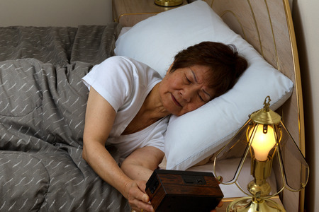 sleep: Senior woman looking at alarm clock during night time. Insomnia concept.