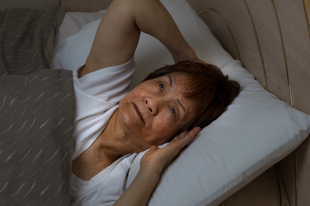 Close up of senior woman, eyes open looking upward, trying to fall asleep. Insomnia concept. Stock Photo