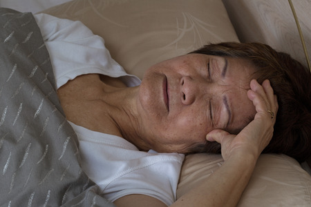 health concern: Close up of senior woman, eyes close, trying to fall asleep. Insomnia concept. Stock Photo