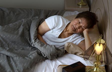 persona enferma: Mujer mayor Restless mirando cama de pie durante la noche. Concepto de insomnio.