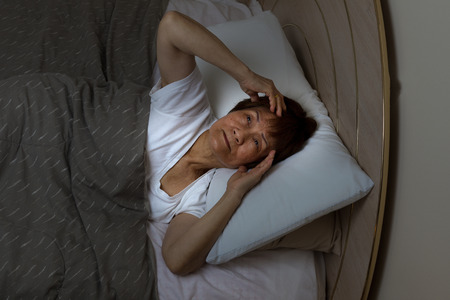 sleep: Top view of a senior woman staring at ceiling of bedroom during night time. Insomnia concept. Stock Photo
