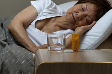 sleep: Close up of an open bottle of medicine and a glass of water on nightstand with senior woman sleeping in background. Sickness concept. Stock Photo