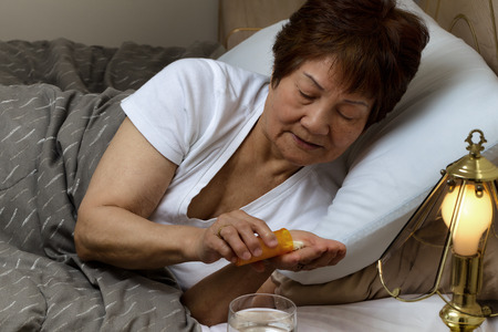 sleep: Close up of senior woman, taking medicine out of bottle, while in bed. Sick concept.