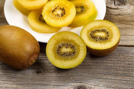 kiwi: Close up of freshly sliced golden kiwi on rustic wood.