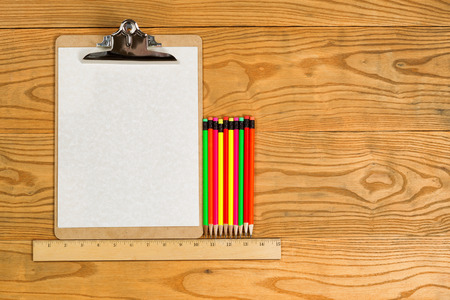 ruler: Top view of traditional clipboard, blank paper, ruler, and colorful pencils on wooden desktop.