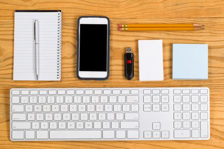 teclado: Alto �ngulo de vista de una computadora de escritorio altamente organizado que consiste en el teclado del ordenador, l�pices, pluma, tel�fono celular, bloc de notas, tarjetas de visita y unidad de disco USB. Dise�o horizontal. Foto de archivo