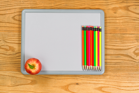 white board: Top view of colorful pencils and apple on white board. Back to school concept. Stock Photo