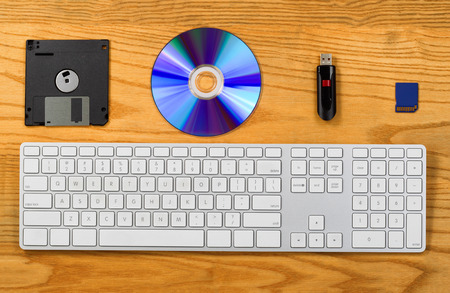 Top view of desktop with keyboard, diskette, CD, thumb drive, and Flash disk. Concept of portable data storage device with technology changes.