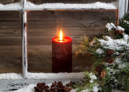 white candle: Decorated window with glowing red candle, selective focus on flame and top part of candle, pine tree, cones and snow outside. Christmas concept.