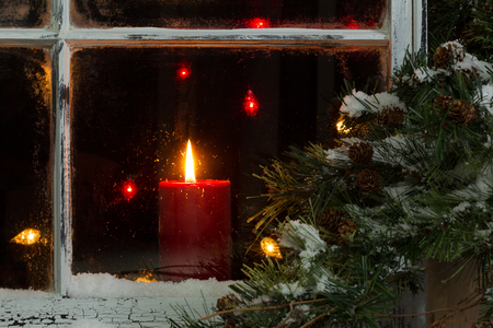 Close up of a red candle, selective focus on flame and top part of candle, glowing in window with pine tree and snow outside. Christmas concept. Stockfoto