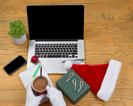 pencil plant: High angled view of hands wearing white gloves while preparing to drink hot chocolate with computer, present, cap, notepad, pencil and plant on desktop. Christmas concept of Santa Claus office. Stock Photo