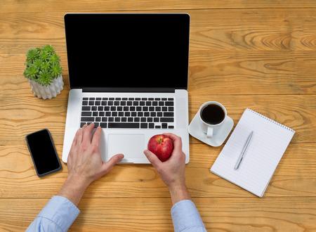 teclado de computadora: Alto ángulo de vista masculino celebración de manzana mano mientras se escribe en el teclado del ordenador.