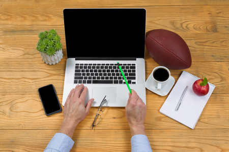 pencil point: High angled view of male hand holding pencil, point at screen, while typing on computer keyboard. Game plan concept with football in background.
