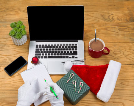 High angled view of Santa Claus writing his gift list with hot chocolate, computer, present, cap, notepad, pencil, cell phone, reading glasses and plant on desktop. Christmas concept of Santa Claus office.