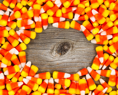 candy border: Border circle of candy corn on rustic wood.