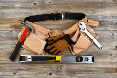 business tool: Traditional leather tool belt with tools on rustic wooden floor.