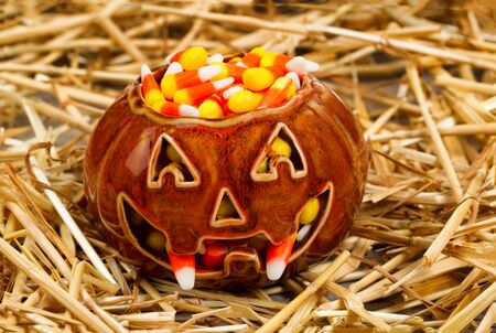 candies: Vista frontal de la calabaza de miedo con colmillos llenos de dulces de maíz en la paja. Concepto de Halloween.