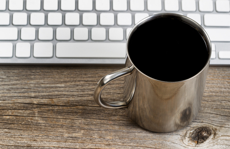 telecommute: Selective focus on lip of coffee mug with partial keyboard in background. Layout in horizontal format on rustic wood. Stock Photo