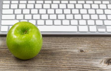 Selektivní zaměření na zralé zelené jablko s částečným klávesnicí v pozadí. Rozložení v horizontálním formátu na rustikální dřevo.