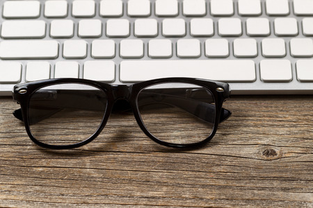 Selective focus on reading glasses with partial keyboard in background. Layout in horizontal format on rustic wood.