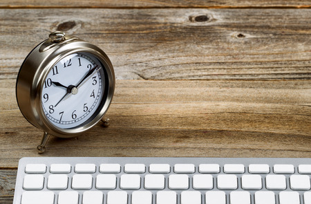 foreground focus: Selective focus on desktop retro metal clock with partial keyboard in foreground. Layout in horizontal format on rustic wood. Stock Photo