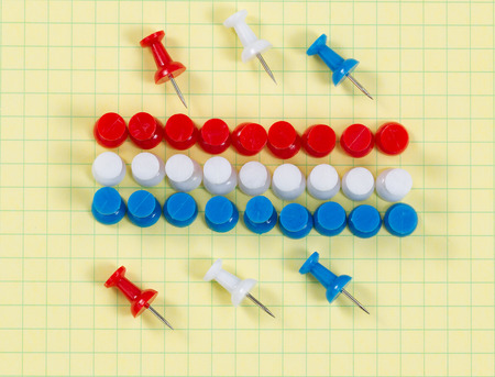 yellow thumbtacks: Close up of red, white and blue thumbtacks pinned on yellow graph paper. Patriotic concept for USA colors. Stock Photo
