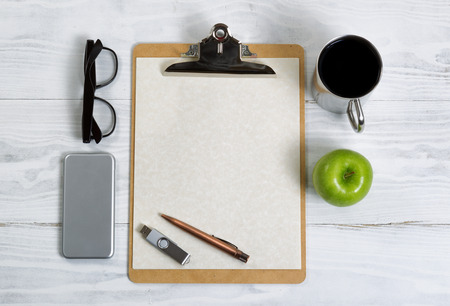 pluma y papel: Top view of clipboard with coffee, pen, paper, apple, thumb drive, cell phone and reading glasses.