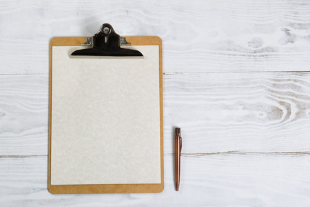 pluma y papel: Top view of clipboard with antique pen, paper on white desktop.