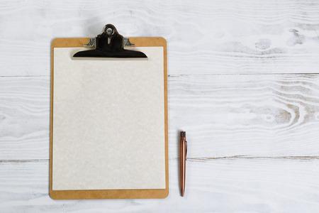 grabado antiguo: Vista superior de portapapeles con la pluma antigua, papel en el escritorio blanco. Foto de archivo