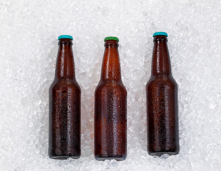 Bottles of beer, lying on side, cooling down on pile of ice. Archivio Fotografico