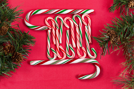 peppermint candy: Peppermint candy canes with evergreen branches as side borders on red background. Christmas concept.