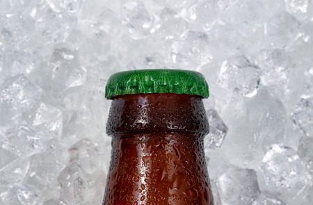 single beer bottle: Close up of a single partial bottle of beer cap cooling down on pile of ice. Layout in horizontal format. Stock Photo