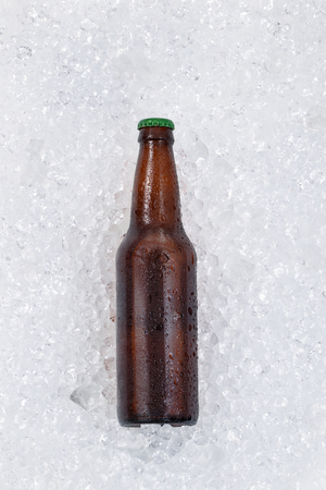 vertical format: Single bottle of beer cooling down on pile of ice. Layout in vertical format. Stock Photo