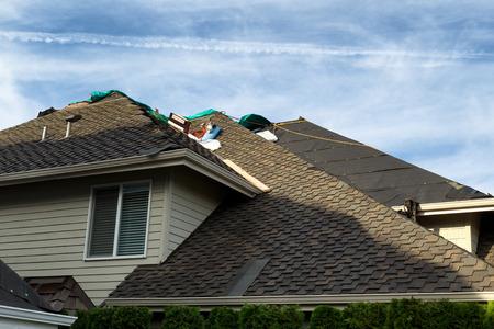 交換表示新しい帯状疱疹、フェルト紙およびツールをされている屋根が付いている家。背景の青い空。